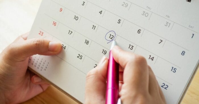 person circling a date on a calendar